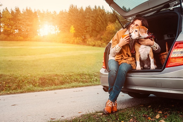 Woman-with-dog-sits-in-car-trunk